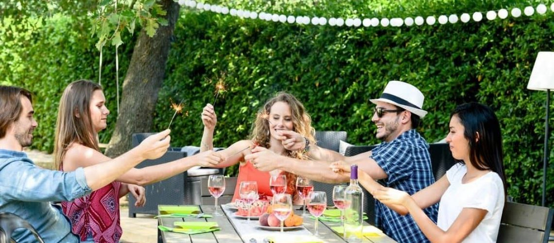 group of friends having fun picnic lunch party outdoor in backyard during summer holiday vacation